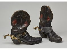 Pair of Old Western Cowboy Boots with Hercules Bronze Spurs. The black leather cowboy boots with diamond inset panels, were acquired with the other three cowboy items in the sale. The boots were soled with rubber years ago. The Hercules bronze Indian head medallion spurs are a bit tarnished. The boots show wear from normal use and measure 11.4 inches long. Circa 1920-40.