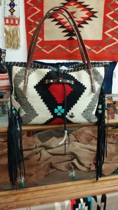 Ooo So Santa Fe ...All of my bags are made by hand and each is one-of-a-kind, incorporating a combination of retired vintage Navajo blankets / rugs, vintage or gently-used horse tack, and deer, elk or cowhide leathers. I embellish the bags with vintage trade beads, turquoise, coral, nickel silver/German silver Concho buttons, nickel silver spots/studs, and deer antler tips. Pillow ticking or unbleached muslin is used for the linings, and all the fringe is hand-cut. www.ooososantafe.com