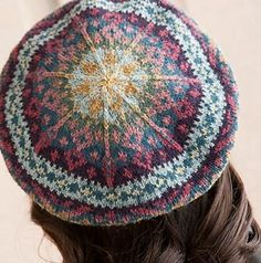 Ravelry: Faded Splendor Tam pattern by Janine BajusThis pattern is available for download for $5.50.     The tam includes traditional Fair Isle motifs and muted colors inspired by the lovely shades of faded Persian rugs. It has three parts: the band, the body, and the wheel at the top, which is formed by seven double decreases every other round. The body is a straight tube; the distinctive tam shape is created by blocking after the knitting is finished.