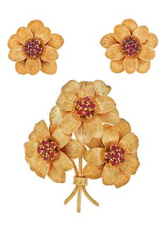 A CHARMING TIFFANY SET  A pretty floral Tiffany set made with 18 karat gold set with a cluster of 6 rubies in the centre of each flower. With three flowers comprising the brooch and a flower for each earring, the set contains 30 rubies weighing a total of approximately 7 carats. The earrings and the brooch are all marked 'Tiffany Italy' 18kt, and circa 1980s