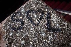 Rustic Wedding - the bride and groom's initials embedded into the river rock at the entrance to the venue