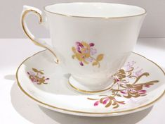 Gracious white is the perfect backdrop for the hand painted gold and lilac tea cup and saucer. Royal Grafton Fine Bone China of England crafted this elegant teacup and saucer. Measurements: The saucer is 5.5 in diameter. The cup is 3 high and 3.25 from rim to rim. This English tea