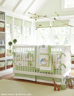 Green and white create a fresh feeling. A vintage-style crib with turned spindles is complemented by Beatrix Potter's timeless characters and a tailored crib skirt. We made a handcrafted mobile out of a branch with fabric leaves and small birds. Green roman shades, a green rug and green gingham storage basket liners complete the room.