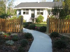 Custom wood saddled fence for front sidewalk entrance by Mossy Oak Fence Company, Orlando and Melbourne, FL