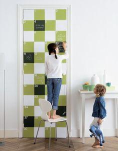 Un calendrier peint à la peinture ardoise vert anis et kaki sur une porte blanche