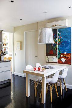 Cocina con comedor integrado. El cuadro 'Jarrón fragmentado', de Alejandra Seeber, aporta color a un conjunto donde predominan los tonos neutros. Mesa rectangular con sillas 'Eiffel' (Manifesto) y una lámpara colgante de la colección 'Mimbre' (La Feliz).
