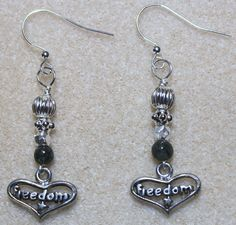 "Handcrafted by Teal Palmetto, LLC. Wear these earrings to express your love for (or desire for) freedom!  Heart-shaped ""Freedom"" charms dangle at the ends of these earrings, which are topped with olive green glass and silver-tone metal beads.  The pair has silver-tone fish hook ear wires.  Price: $13"
