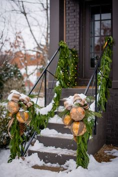 Decorating an outdoor stairs - fresh greens garland, sugar pinecones, shiny ornaments & glittered burlap ribbon. I'd love it w/ red for my house.