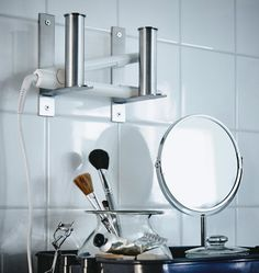 Two IKEA GRUNDTAL toilet roll holders are mounted vertically to a bathroom wall and used to hold a flatiron.