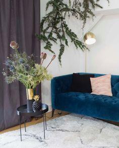 Incontournable tendance deco le canapé en velours choisit en bleu canard permet de rehausser la déco dans un salon hivernal cosy et hygge