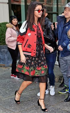 SELENA GOMEZ: is unmissable in her floral print party dress, Coach varsity jacket, ankle-strap stilettos and ruby-tinted Garrett Leight X Clare V. frames.