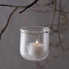 "Textured glass surrounds a glowing tea light inside this petite vessel, each one topped with a wire handle for hanging indoors and out.- Glass, metal wire- Wipe clean with dry cloth- Indoor or outdoor use- ImportedGlass: 3""H, 2.5""D, 2.75"" diameterHandle: 3.5""H"