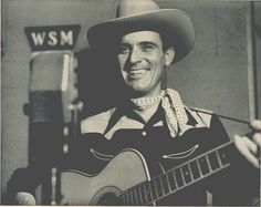 Ernest Tubb (1914-1984), holding guitar, standing in front of a WSM radio microphone