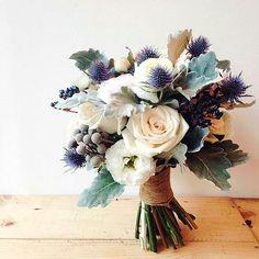 Hand Tied Wedding Bouquet Featuring: White Lisianthus, White Roses, White Ranunculus, Cream Roses, Blush Ranunculus, Blue Eryngium Thistle, Dark Blue Privet Berries + Dusty Miller >>>>