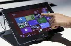 A person tries a Samsung tablet computer running Windows 8 at the launch of Microsoft Windows 8, in New York, Thursday, Oct. 25, 2012. Windows 8 is the most dramatic overhaul of the personal computer market's dominant operating system in 17 years. (AP Photo/Richard Drew)
