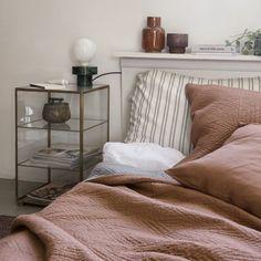 Du linge de lit terracota House Doctor dans la chambre avec un chevet en verre et laiton