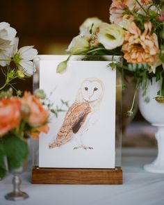 Instead of traditional numerals, large prints of hand-painted birds in wood-based picture frames adorned Jocelyn and Graham's tables and served as identifiers for the corresponding escort cards given to each guest. The illustrations (done by the bride's aunt Haven) were of species often seen on Martha's Vineyard. The original paintings were framed and hung in the newlyweds' home.