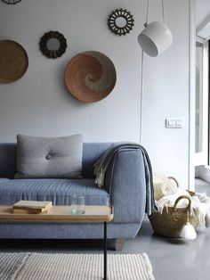 AIM pendant lighting in white complement the bright and airy aesthetic in this cozy living room with unique wall decor a large blue sofa.