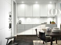 Valkoinen keittiö, jossa valkoiset kodinkoneet, mustanruskeat nahkatuolit ja ruokapöytä.