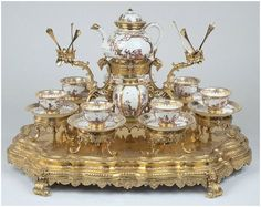 Porcelain tea service circa 1725-30 by Unknown artist.   This unique tea service includes a teapot, an angular tea caddy, an oval sugar bowl and six cups and saucers.  Note the spoon holders.