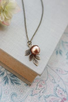 A beautiful acorn necklace made with a large rose gold finish swarovski pearl, with a nicely plated oxidized brass acorn