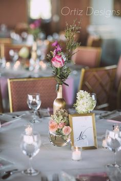 A DIY centerpiece using spray-painted wine bottles and vases from thrift store.  Flowers used included hydrangea, dave austin roses, spray roses, and stock.  Tags: pink, gold, wedding, diy