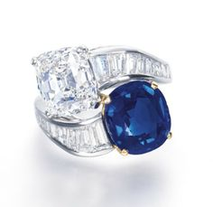 AN IMPORTANT SAPPHIRE AND DIAMOND RING, BY BULGARI   Designed as a crossover ring, each terminal set with a cushion-shaped sapphire weighing 5.79 carats and a cushion-shaped diamond weighing 5.01 carats, joined to the baguette-cut diamond quarter-hoop, mounted in platinum and 18k yellow gold, ring size 6¾, in black leather Bulgari case    Signed Bulgari
