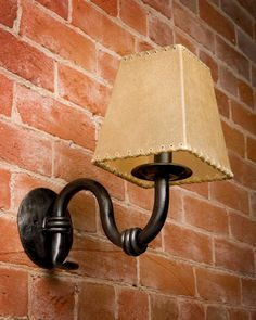 Iron wraps accent the symmetrical curves of this beautiful handmade wall sconce. The hand-forged iron backplate easily mounts to any standard electrical junction box. This fixture is rated for a 45 watt candelabra bulb. Shade is not included but a square or round rawhide shade is available.