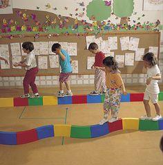 Crea en el piso un camino de bloques en altura para que los niños lo recorran haciendo una fila, respetando y esperando a quien tienen delante de ellos.  Este juego fomenta además, el equilibrio y control motor del cuerpo.