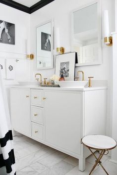 Black and white bathroom features white walls finished with black crown moldings lined with a white vanity by Kohler adorned with gold knobs topped with his and her round bowl sinks, Kohler Conical Bell Sinks, paired with Purist Widespread Bathroom Sink Faucets Vibrant Moderne Brushed Gold situated below white vanity mirrors illuminated by Kohler Purist Single Wall Sconces Vibrant Moderne Brushed Gold alongside a towel rail draped in black and white monogram towels and a brass and marble…