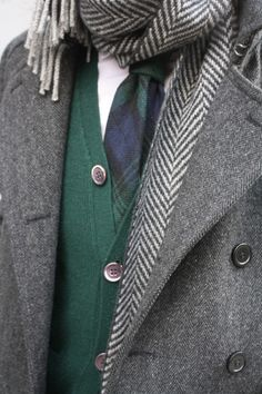 grey coat and herringbone patterned grey scarf, green cardigan and black watch plaid tie.