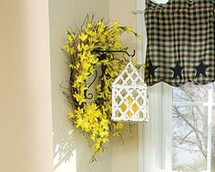 Mount a decorative planter hook on an interior wall to support a lantern-style candleholder. Place a forsythia wreath around the hook for more spring flair. • To see more of this photo and find out more about the items shown, turn to page 66 of our May 2015 issue or page 6 of our online Craft Fair, www.countrysampler.com/craftfair