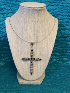 This item features a large cross with paper beads. The paper beads are handcrafted in our shop. The beads are pictured in shades of gray but other