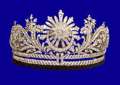 """The trademark tiara of the Queens of Malaysia is known as the Gandik Diraja. Crafted from platinum & diamonds, it incorporates several traditional motifs: a central star with a crescent and the swiriling """"awan larat"""" design. The current version was remounted from a previous diadem by Garrard in 1984 and is designed to break down into a locket and set of brooches."""