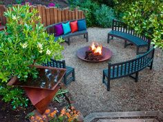 The contemporary seating around the copper fire pit allows for a cozy large gathering. The fire pit brings warmth, while a copper water feature adds dimension to the space. Vibrant pillows are the only touches of color in the outdoor space. Design by Jane Ellison