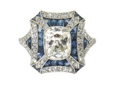 A ravishing recreation of the Art Deco style's gorgeous geometry, this sapphire and diamond ring is splendid for the vintage-inspired vixen. An antique cushion cut diamond takes center stage in a beautiful bezel setting surrounded by sapphire accents and a dash of diamonds adding a sculpted structure to the style.