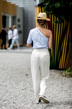 blue one-shoulder top, high-waisted trousers, panama hat