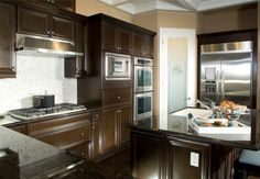 Dark chocolate wood cabinetry surrounds white tile backsplash over dark tile flooring in this cozy kitchen with marble countertops.