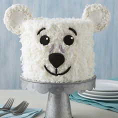 Whether it's a birthday, a Christmas party or just a reason to celebrate the beauty of winter, this Polar Bear Cake is a cute and fun way to liven up any party! Decorated with flaked coconut, this Polar Bear Cake makes a great winter treat served alongside a hot cup of cocoa. Use your favorite cake recipe to make this three-layer cake, or mix and match cake layers to reveal a colorful surprise once you cut into this treat! An easy project for beginning decorators, this Polar Bear Cake…