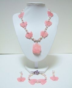 $195.00 Pink Rose Quartz Gemstone hand carved rose pendant and butterflies, with white freshwater pearls, and silver plated beads. Matching earrings and bracelet. COME SEE MORE UNIQUE OOAK JEWELRY AT: https://www.etsy.com/shop/JewelrybyIshi #cloisonnejewelry #freshwaterpearls #gemstonejewelry #carvedcinnabar #abalonejewelry #lampworkglass #dichrociglass #coraljewelry #shelljewelry #vintagejewelry #handmade #handbeaded #necklace #earrings #bracelet #brooch #beadedbags #eveningbags