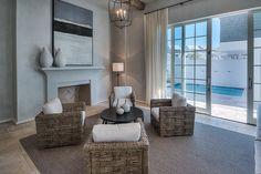 White, glass front patio doors dressed in long ivory curtains open to a living room featuring four natural woven accent chairs positioned around a round black coffee table sat on a brown bound sisal rug lit by a black caged chandelier.
