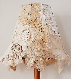 """Doily Lamp Shade: For the lamp shade, remove the original fabric, leaving only the frame. Pin small doilies around the top, and then to one another, for a skirtlike effect. Remove pinned doilies. Machine-stitch together. Slip """"skirt"""" over frame; hand-stitch around frame's top."""