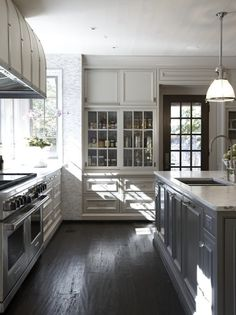 Dark stained floor, grey cabinets and creamy grey/white accent colors = beautiful kitchen!