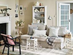 Soggiorno con divano letto beige, sgabelli bianchi usati come tavolini e mobile alto – IKEA