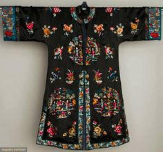 SILK SATIN EXPORT COAT, CHINA, MID 20TH C Black satin w/ blue satin sleeve bands, polychrome silk embroidered figural rondels & scattered flowers, L 44