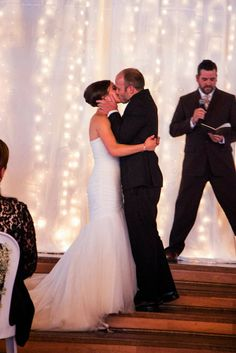 bride and groom kissing twinkle light backdrop wedding ceremony