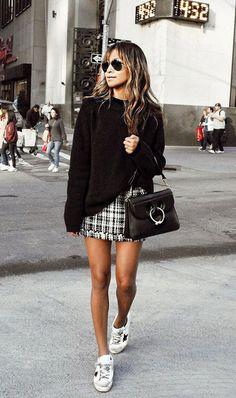 Une mini avec un pull noir et des baskets