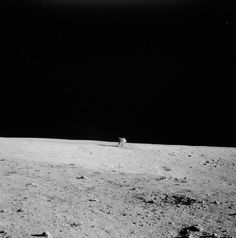 """Distant view of the Lunar Module """"Intrepid"""" near the rim of Surveyor Crater. Surveyor Crater is visible in the foreground. The image was taken during the second EVA of the Apollo 12 mission."""