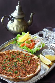 How about some lahmacun? Lahmacun (pronunciation: [lahmaˈdʒun]) is an item of prepared food originating in the early Syrian cuisine of the Levant, consisting of a round, thin piece of dough topped with minced meat (most commonly beef and lamb). Lahmacun is often served sprinkled with lemon juice and wrapped around vegetables, including pickles, tomatoes, peppers, onions, lettuce, and parsley