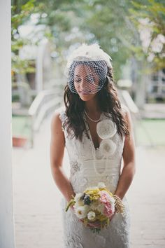bride with lace gown and pink white and yellow flowers